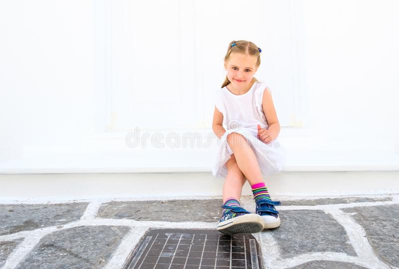 Little pretty blong girl in a white dress sitting outdoor stock image