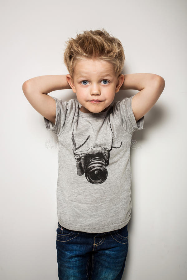 Little pretty boy posing at studio as a fashion model stock photos