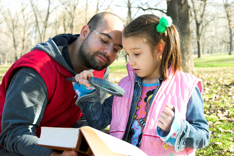 Little pretty child and father reading the book. In the park royalty free stock images