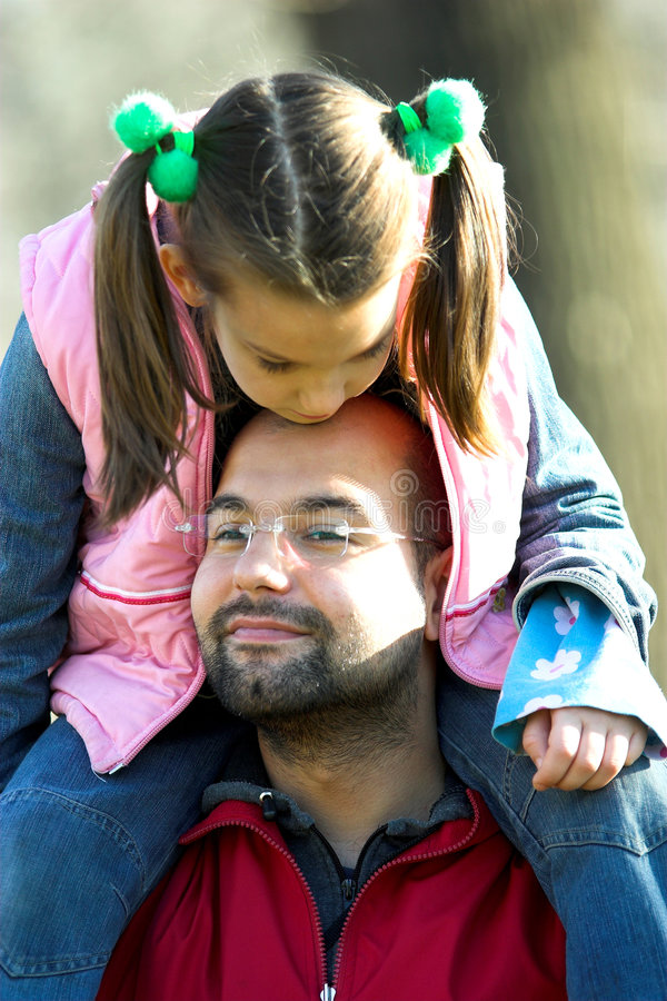 Little pretty child on father shoulder. In the park stock image