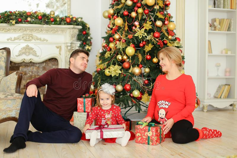 Little pretty daughter sitting with father and pregnant mother near Christmas tree and keeping gifts. stock photos