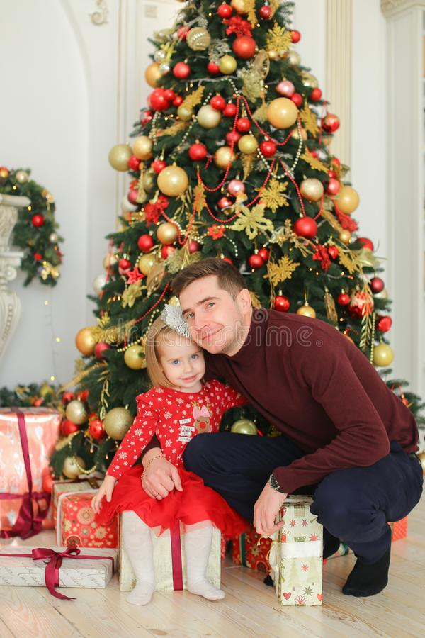 Little pretty daughter wearing red dress hugging father near Christmas tree and presents. royalty free stock photos