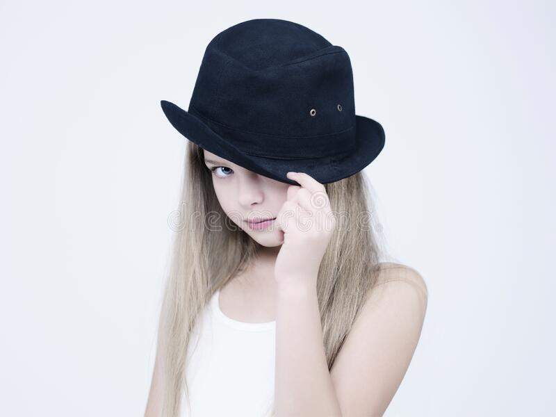 Little pretty girl in black hat. Little pretty girl in black classic hat. Studio ashion photography of kid in white dress. Beautiul model on white background stock images