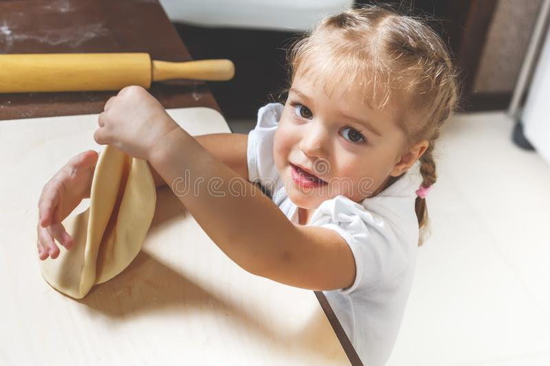 Little pretty girl is cooking dough in the kitchen at home to help her mother stock photos