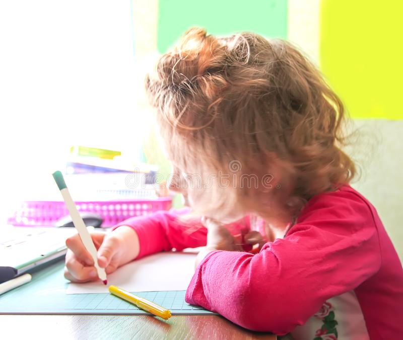 Little pretty girl with curly hair sitting at the desk and writting stock photo