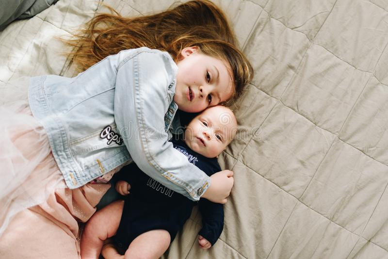 A little pretty girl laying on the bed and hugging her cute baby sibling royalty free stock photo