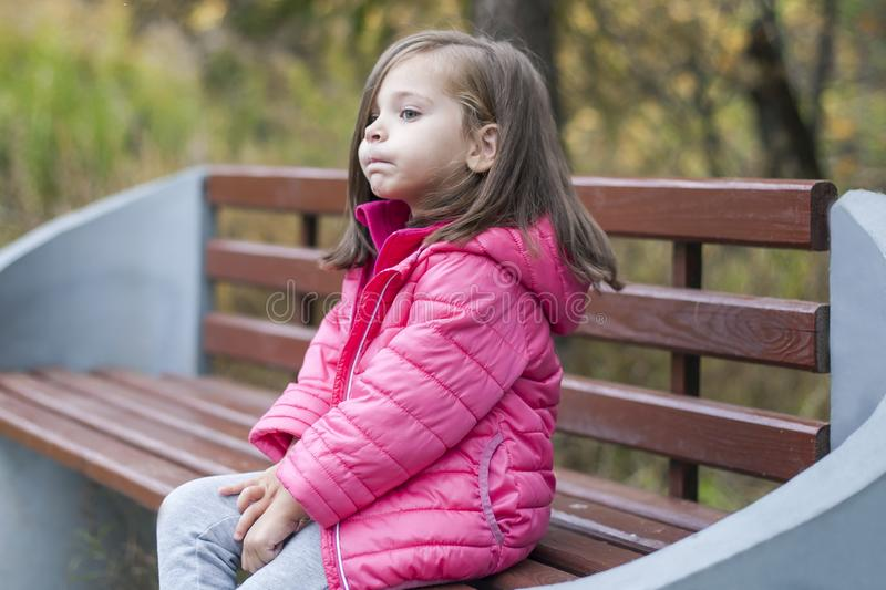 Little pretty girl in a pink coat sitting on a wood bench at the park in autumn. Emotional portrait. Childhood concept stock photography