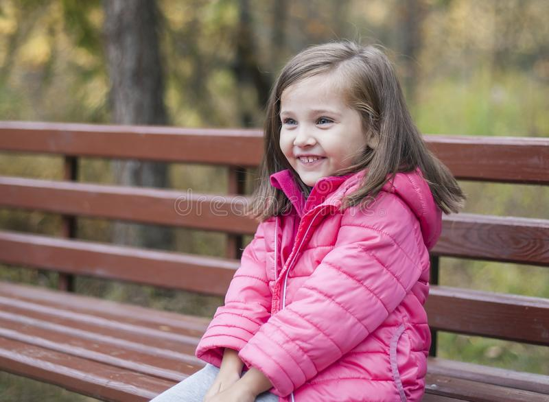 Little pretty girl in a pink coat sitting on a wood bench at the park in autumn. Emotional portrait royalty free stock photos