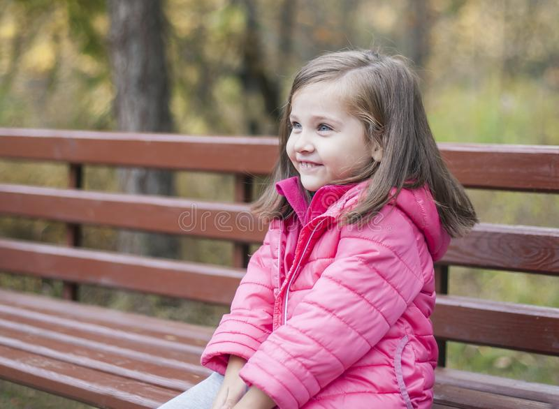 Little pretty girl in a pink coat sitting on a wood bench at the park in autumn. Emotional portrait royalty free stock image