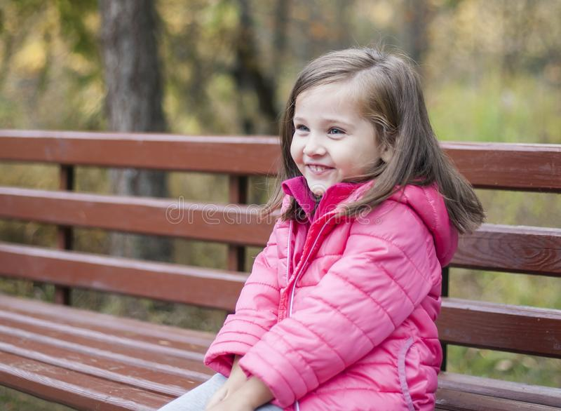 Little pretty girl in a pink coat sitting on a wood bench at the park in autumn. Emotional portrait stock images