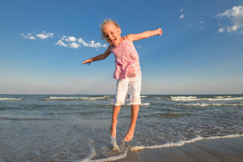 Little pretty girl on summer beach. Cheerful little girl dancing on the background of blue sky and summer sea stock images