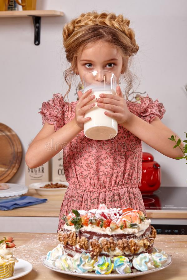 Little girl is making a homemade cake with an easy recipe at kitchen against a white wall with shelves on it. Little pretty girl wearing in a pink dress is stock image