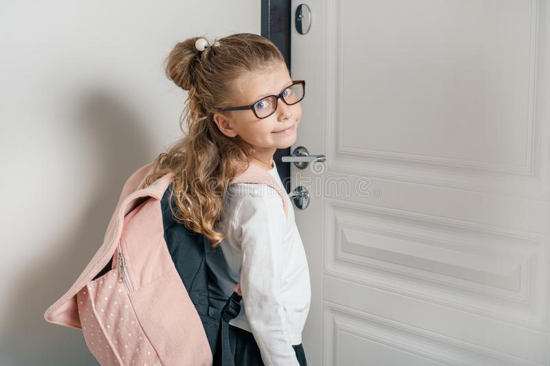 Little pretty girl 6, 7 years old with school backpack. Smiling girl standing near the front door of the house, child goes to royalty free stock photos