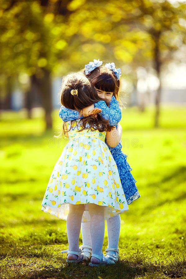 Little pretty girls having fun outdoor. Two cute girls are standing on green grass and hugging. stock photos