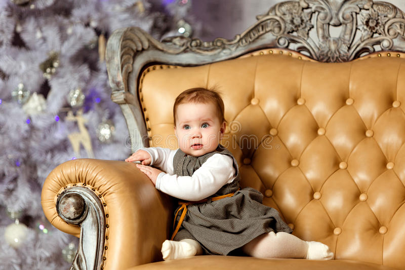 Little pretty and serious girl plump baby sitting in a beige chair against a white Christmas tree in New year stock photos