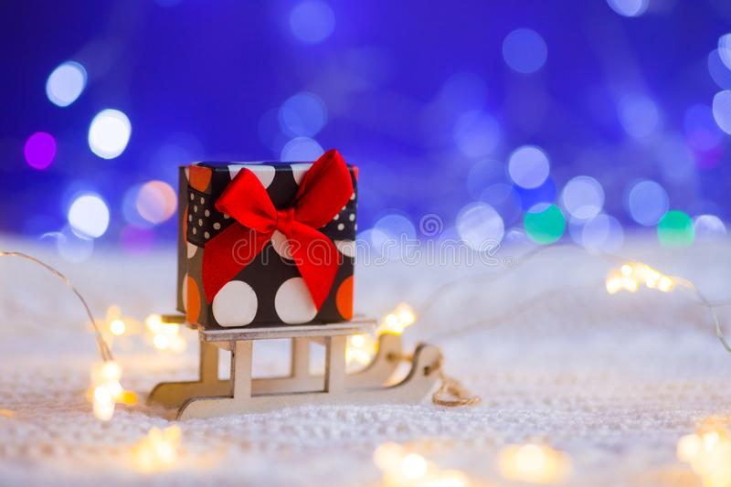 Little pretty spotted gift box with red bow on toy white sled on stock photo