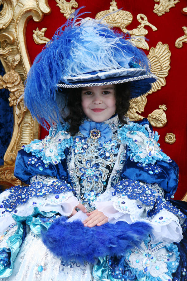 Little princess. Smiling little girl wearing an antique princess dress (sitting on a princess throne and holding a blue fan royalty free stock images