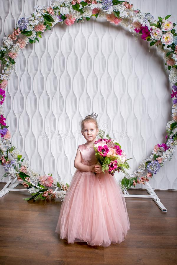A little princess in a beautiful pink dress is holding a bouquet of peonies, magnolia, berries and greenery against a white wall a. Nd floral arch, a general stock photo