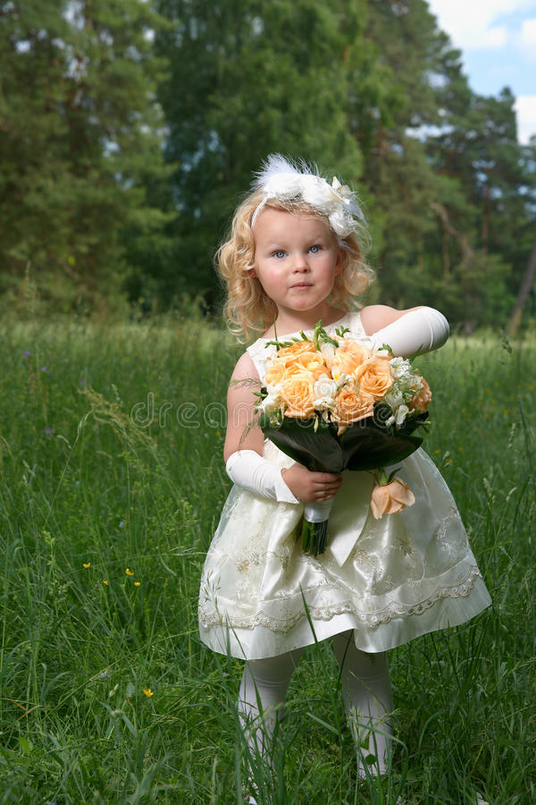 Little princess in a bride dress with a bridal bouquet. Outdoor royalty free stock photos