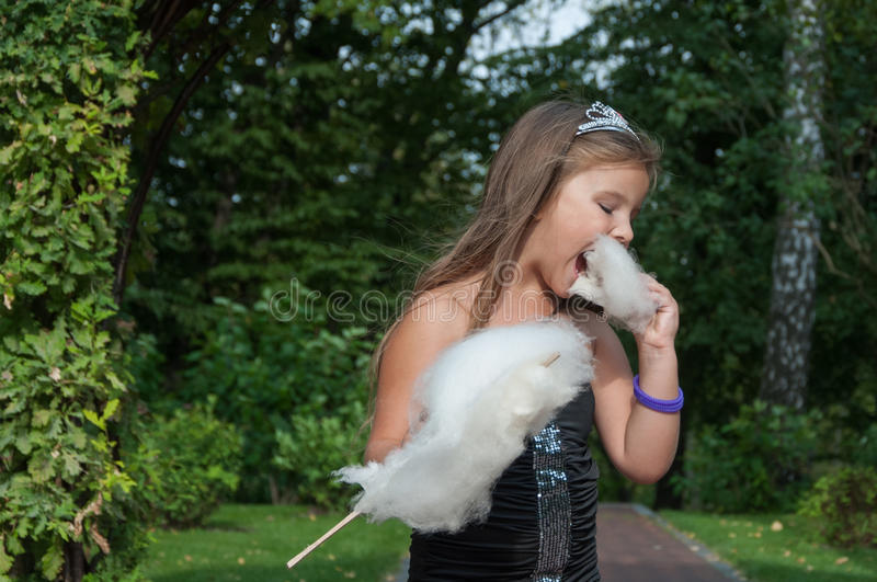Little princess girl eating sweet cotton candy, portrait, summer day in the park stock image