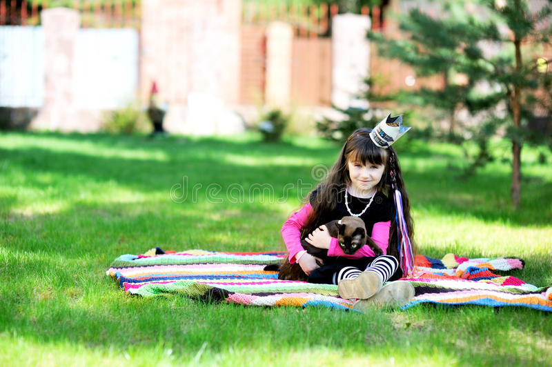 Little princess playing with burma cat outdoors. Beauty little princess with long brunette hair playing with her burma cat in the garden stock photos