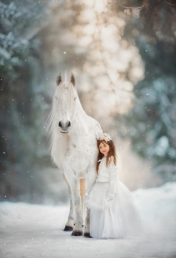 The little princess with an unicorn in the forest. The little girl with a white horse-unicorn in a winter park