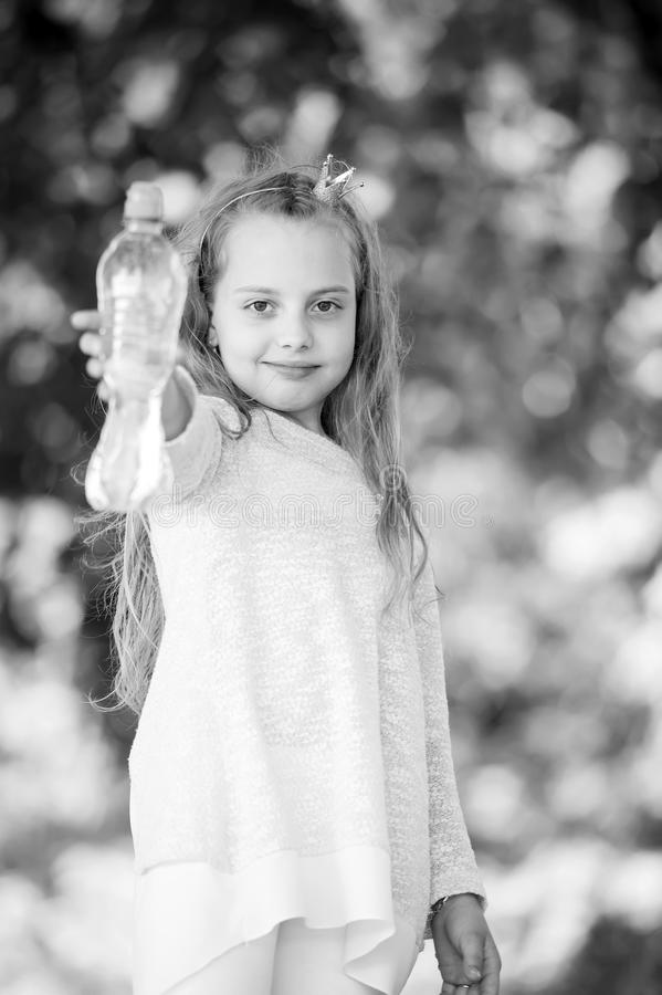 Little princess with water bottle on natural background. Thirsty child hold fresh water for drinking. Thirst and stock photo