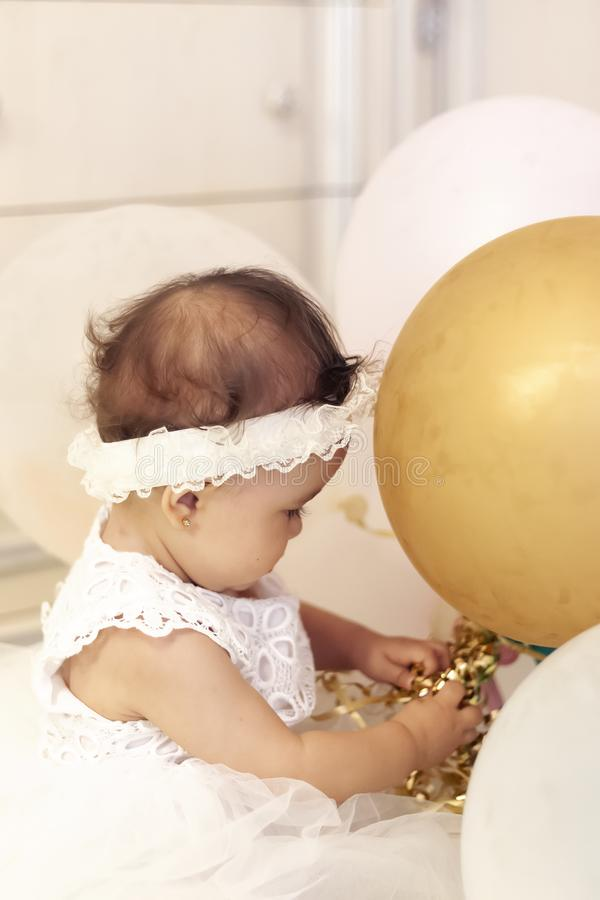 Little princess in white dress playing with air balloons. First birthday royalty free stock images