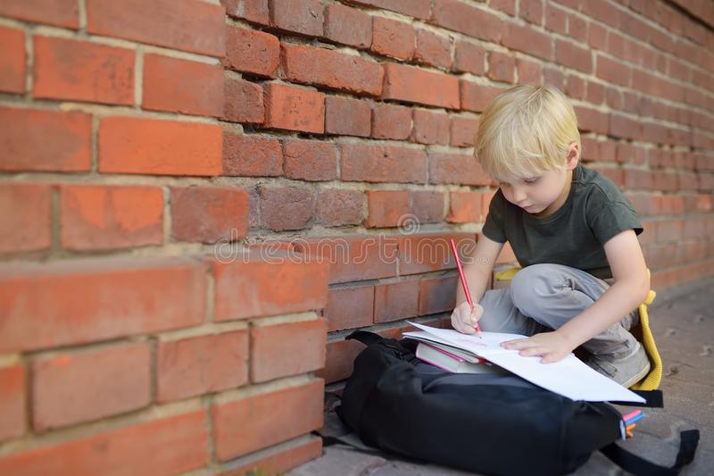 Little pupil doing homework on break near school building. Back to school concept royalty free stock images