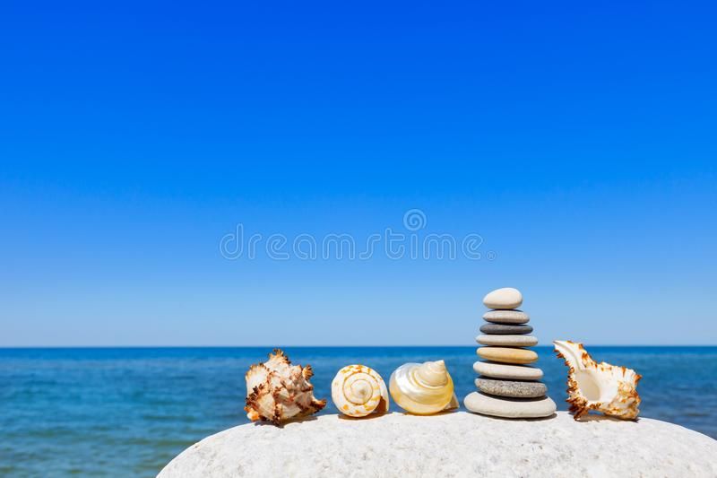 Little pyramid of white pebbles and exotic seashells on the beach on the background of the summer sea and blue sky royalty free stock photo