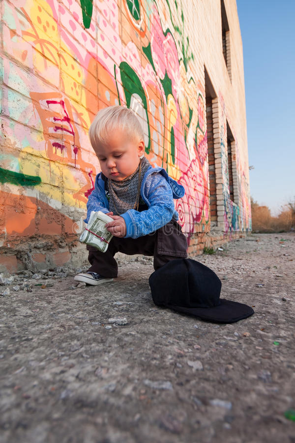 Little rapper. With money in a deserted place royalty free stock image