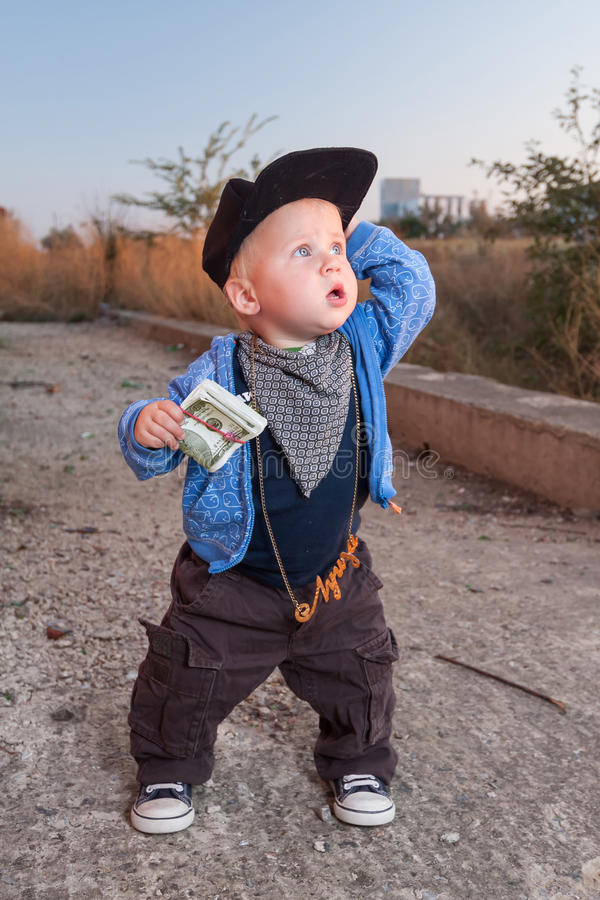 Little rapper. With money in a deserted place royalty free stock photography