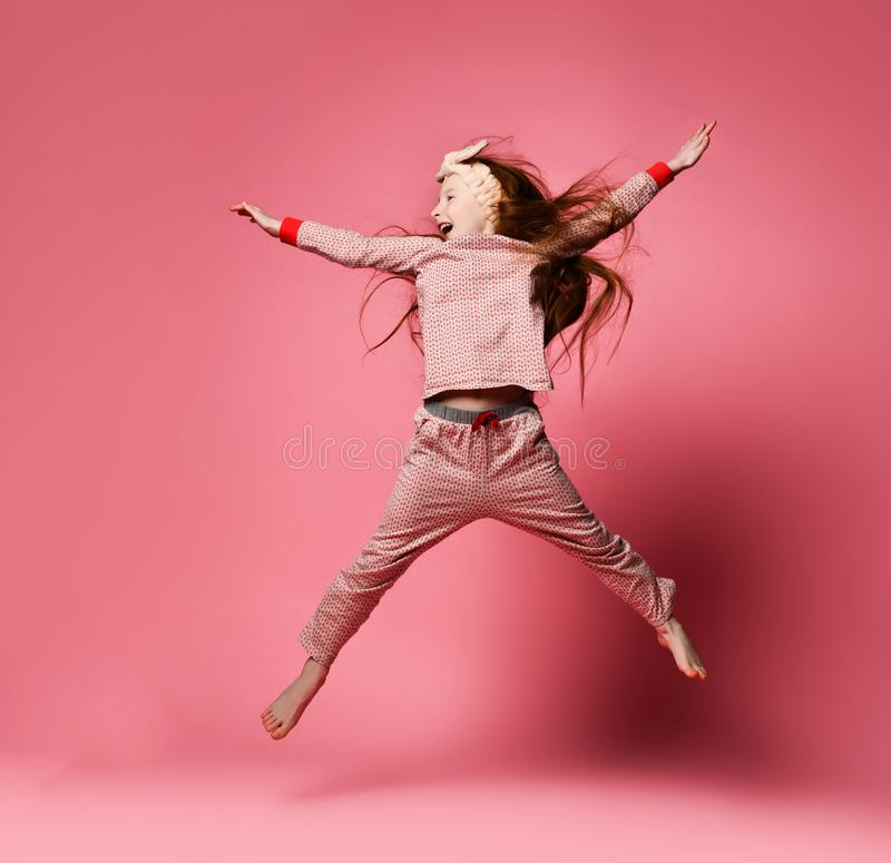 Little red-haired girl in cute pajamas and hair bandages jumping stock images