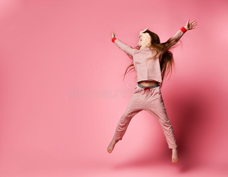 Little red-haired girl in cute pajamas and hair bandages jumping stock photography
