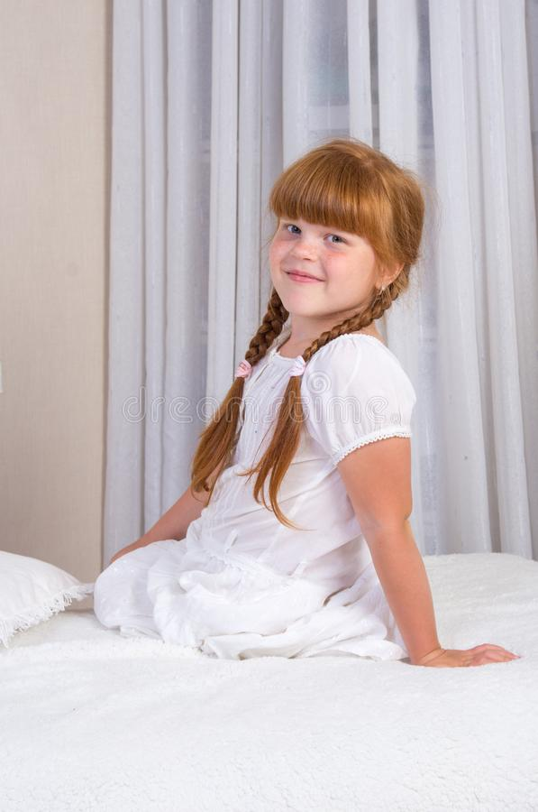 Free Little Red-haired Girl In A White Dress Sitting On The Couch, Leaning On Her Hand Stock Image - 156322021