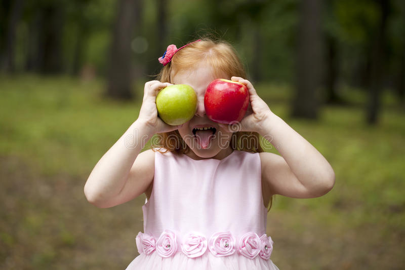 Little red-haired girl in a pink dress holding two apples stock images