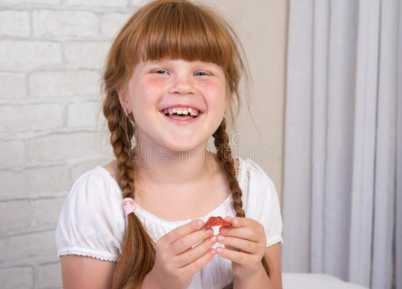 Little red-haired girl in a white dress holds a plate in her hands to correct a bite of teeth stock photo