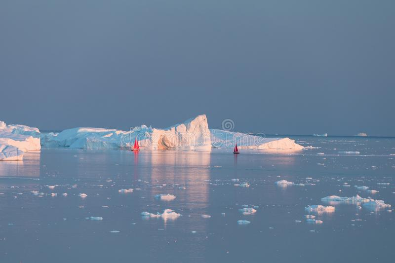 Little red sailboat cruising among floating icebergs in Disko Bay glacier during midnight sun season of polar summer. Greenland. Little red sailboat cruising stock images