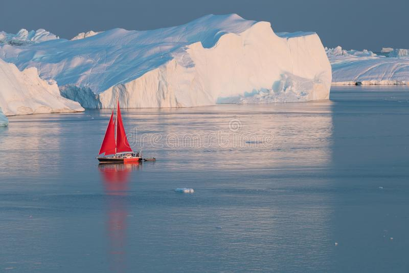 Little red sailboat cruising among floating icebergs in Disko Bay glacier during midnight sun season of polar summer. Greenland. Little red sailboat cruising royalty free stock image