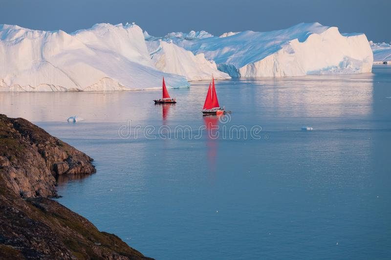 Little red sailboat cruising among floating icebergs in Disko Bay glacier during midnight sun season of polar summer. Greenland. Little red sailboat cruising royalty free stock photography