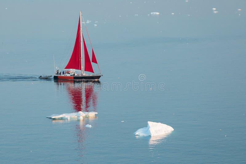 Little red sailboat cruising among floating icebergs in Disko Bay glacier during midnight sun season of polar summer. Greenland. Little red sailboat cruising royalty free stock photos