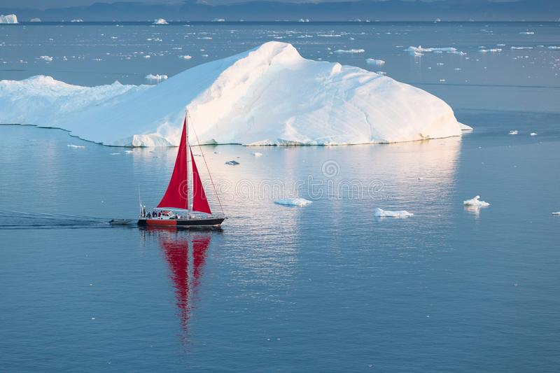 Little red sailboat cruising among floating icebergs in Disko Bay glacier during midnight sun season of polar summer. Greenland. Little red sailboat cruising stock photography
