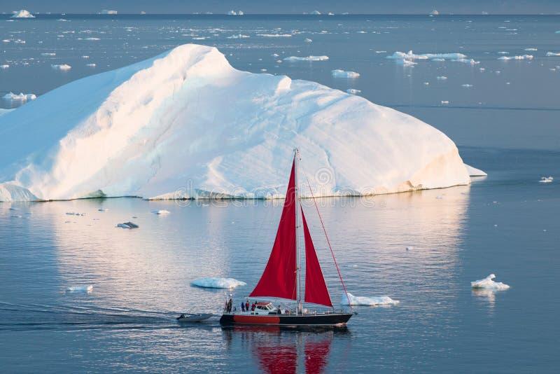 Little red sailboat cruising among floating icebergs in Disko Bay glacier during midnight sun season of polar summer. Greenland. Little red sailboat cruising royalty free stock photo