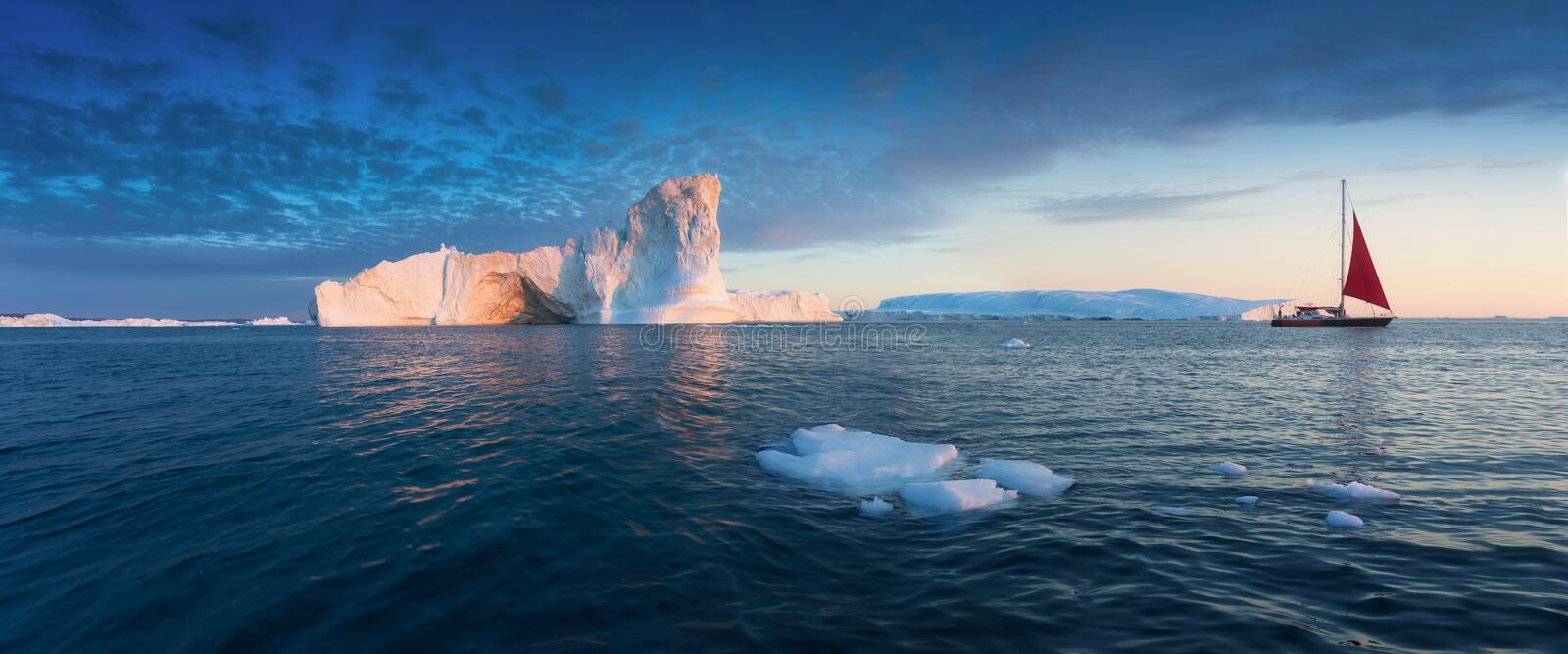 Little red sailboat cruising among floating icebergs in Disko Bay glacier during midnight sun season of polar summer. Greenland royalty free stock images