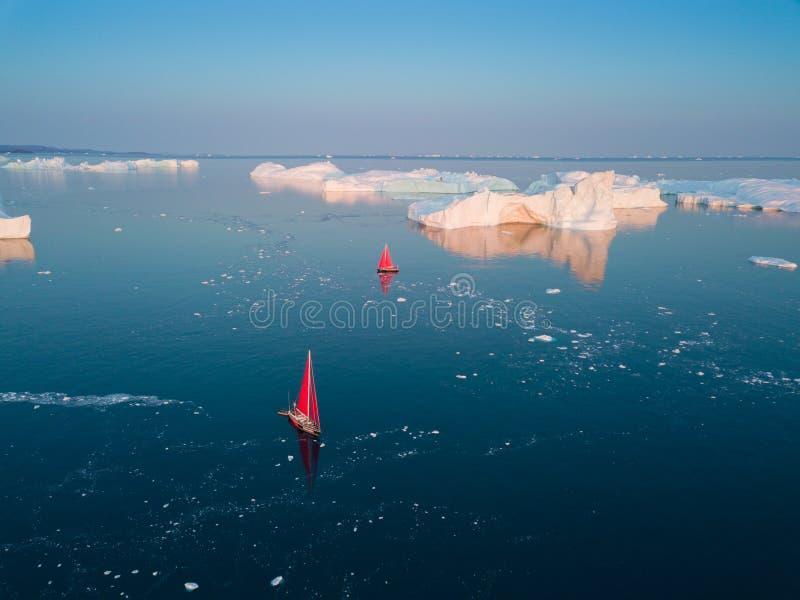 Little red sailboat cruising among floating icebergs in Disko Bay glacier during midnight sun season of polar summer. Ilulissat stock image