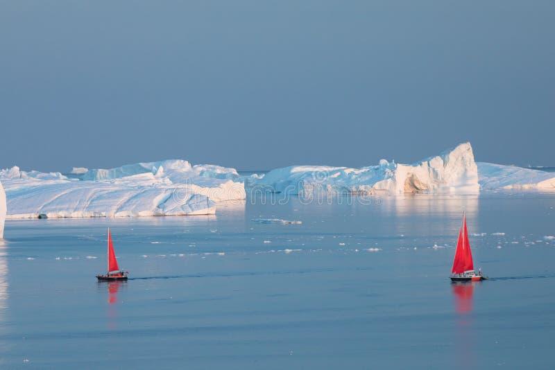 Little red sailboat cruising among floating icebergs in Disko Bay glacier during midnight sun season of polar summer. Greenland. Little red sailboat cruising stock photos