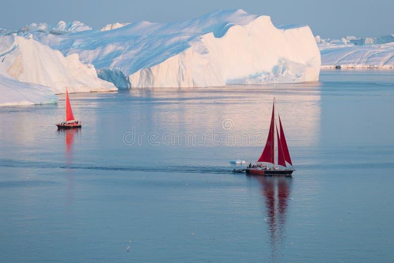 Little red sailboat cruising among floating icebergs in Disko Bay glacier during midnight sun season of polar summer. Greenland. Little red sailboat cruising stock photo