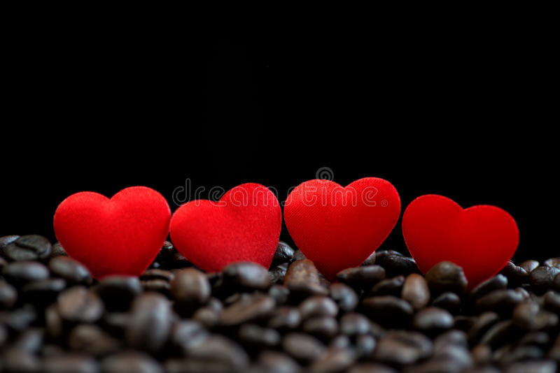 Little red satin hearts on coffee beans isolated on black background, valentines day or wedding day celebrate royalty free stock photography