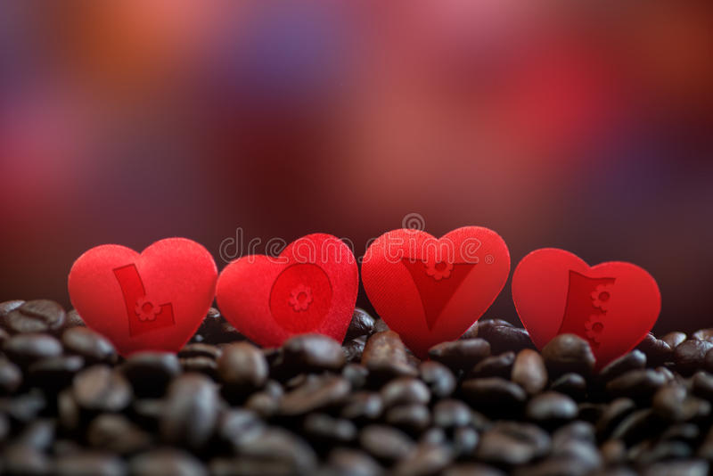 Little red satin hearts with letters on coffee beans, valentines day or wedding day celebrating stock image
