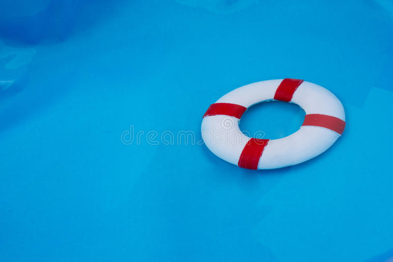 Little red and white color model life buoy. In water royalty free stock photo